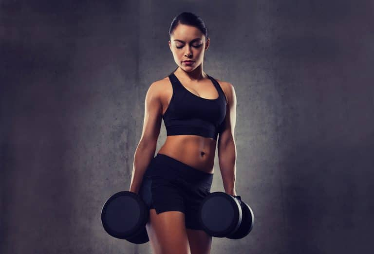young woman flexing muscles with dumbbells in gym